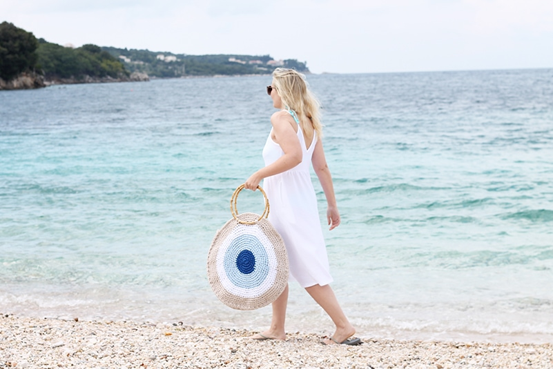 woman walking on the beach wearing an evil eye crochet beach bag with bamboo handles