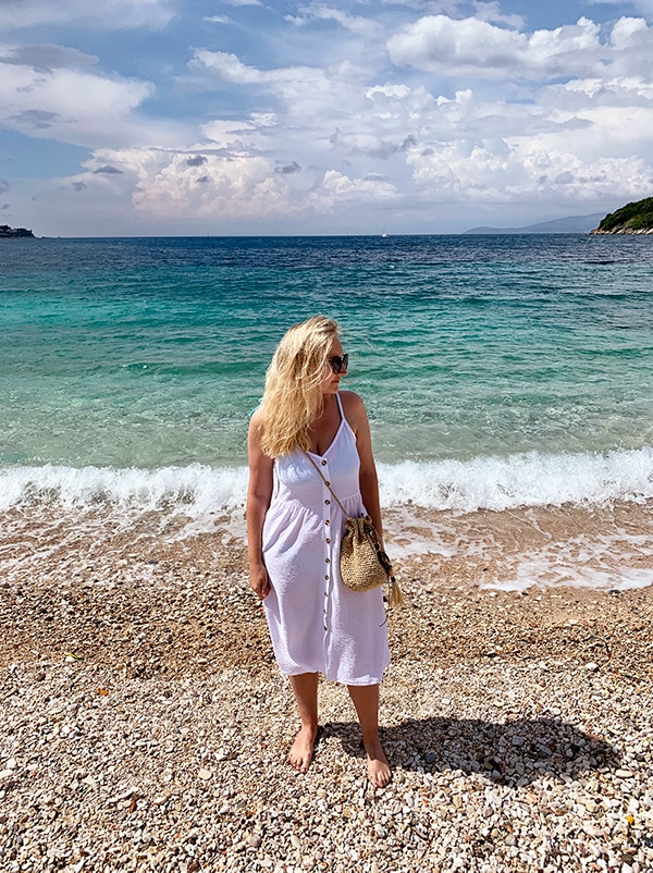 woman at the beach standing in the sea wearing a white dress and a cross body crochet bag