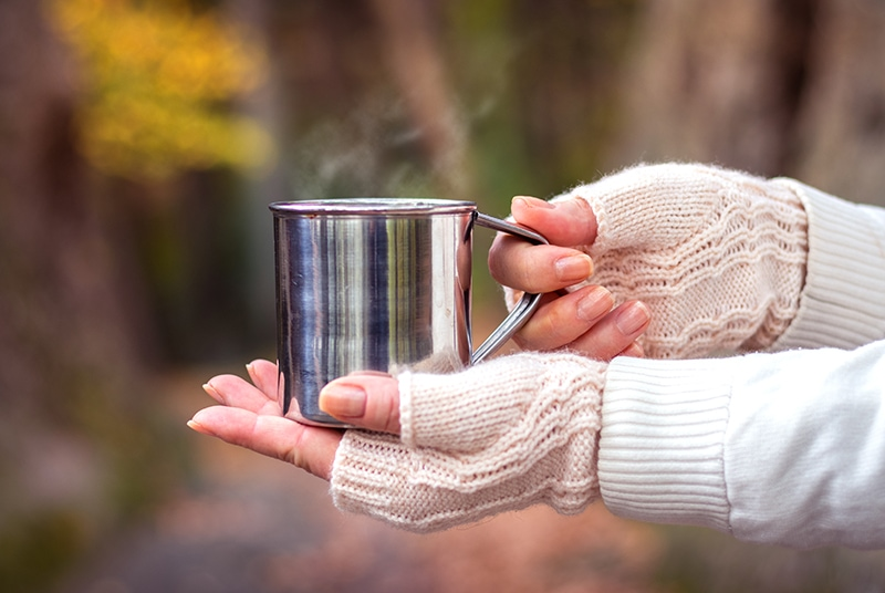 fingerless gloves holding a mug
