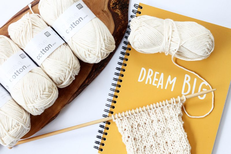 white cotton yarns next to a notebook and knitting