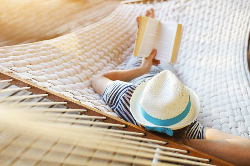 man in a hammock reading a book