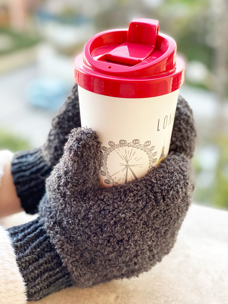 grey knitted mittens holding a coffee cup