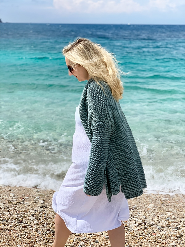 woman on the beach wearing an oversized knit sweater