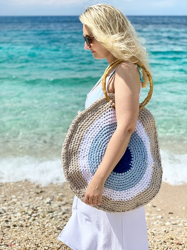 woman wearing a crochet circle beach bag with an evil eye design in Greece