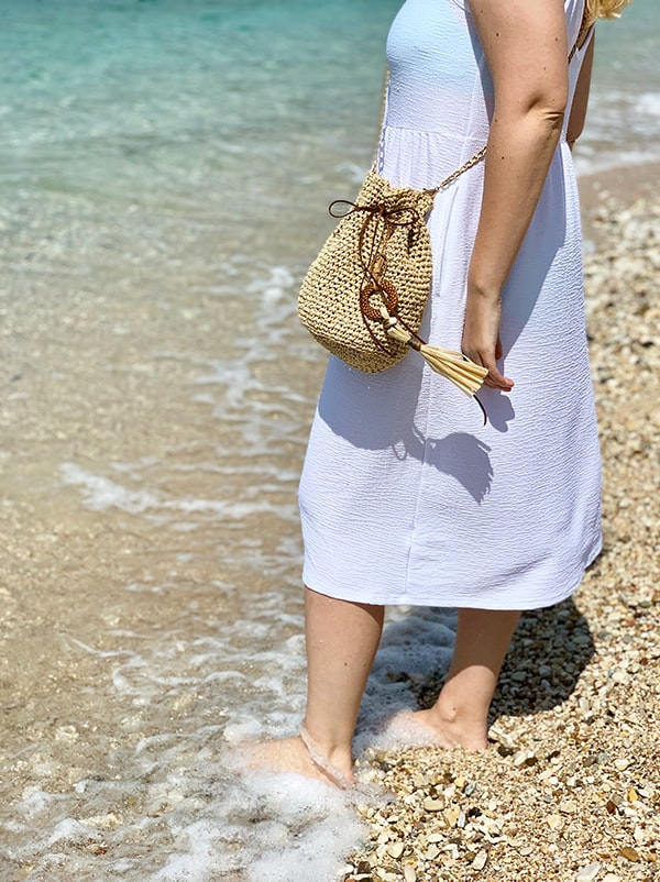 woman at the beach wearing a white dress and a drawstring bag