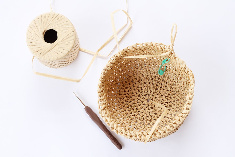 Raffia bag work in progress shot showing the bag being worked in the round.