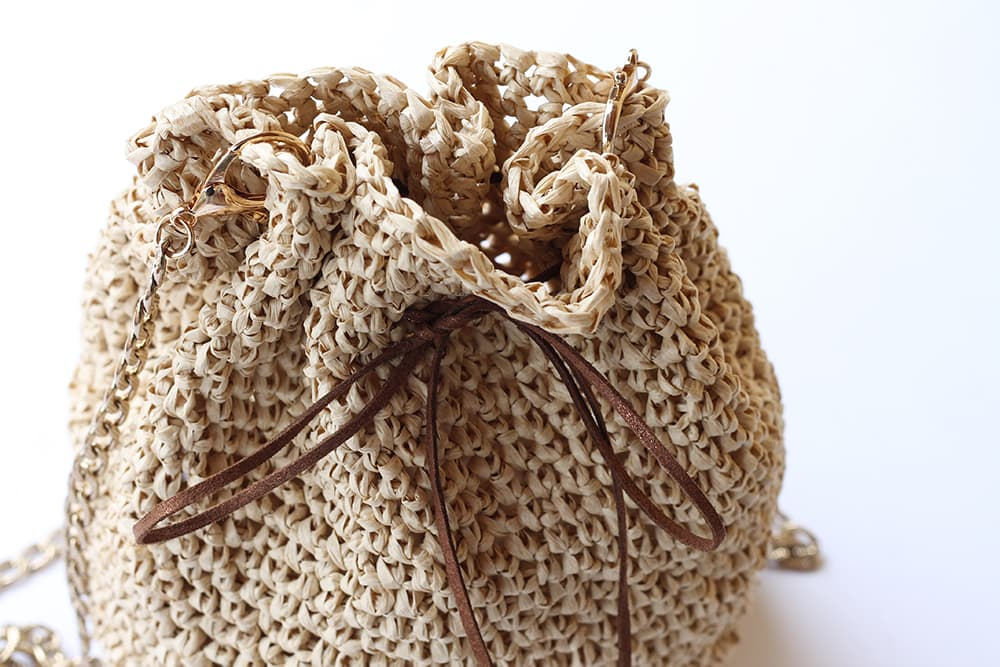 close up of the drawstring raffia bag to see the bag clips and chain