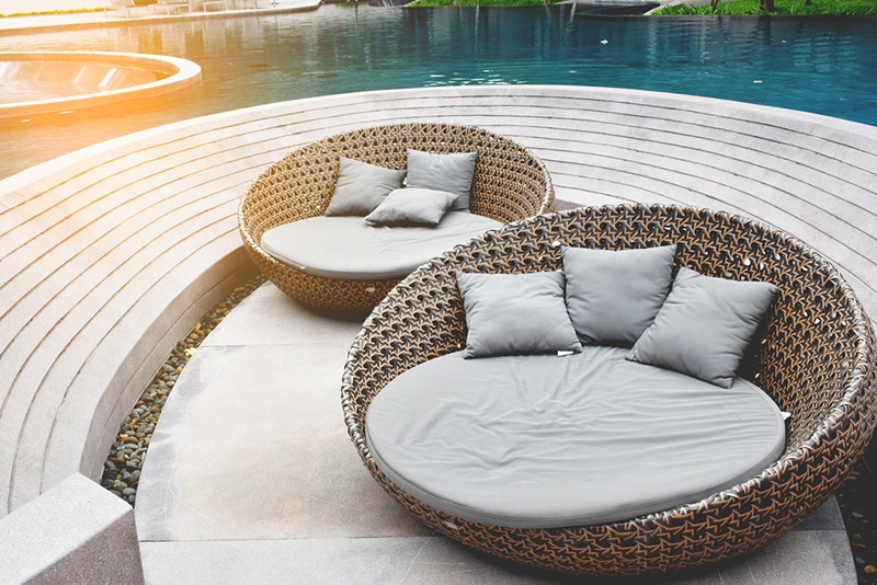 outdoor living wicker furniture inside a pool area