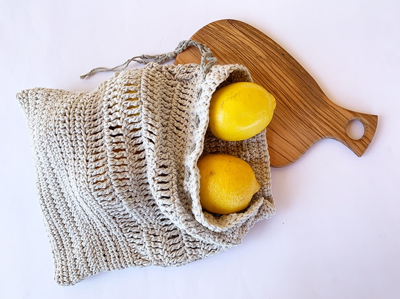 reusable crochet produce bag with lemons and chopping board