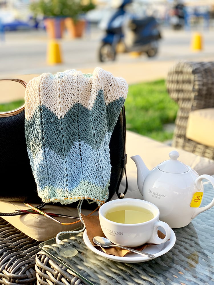 knitted shawl over a bag and teapot and a cup of tea on a table