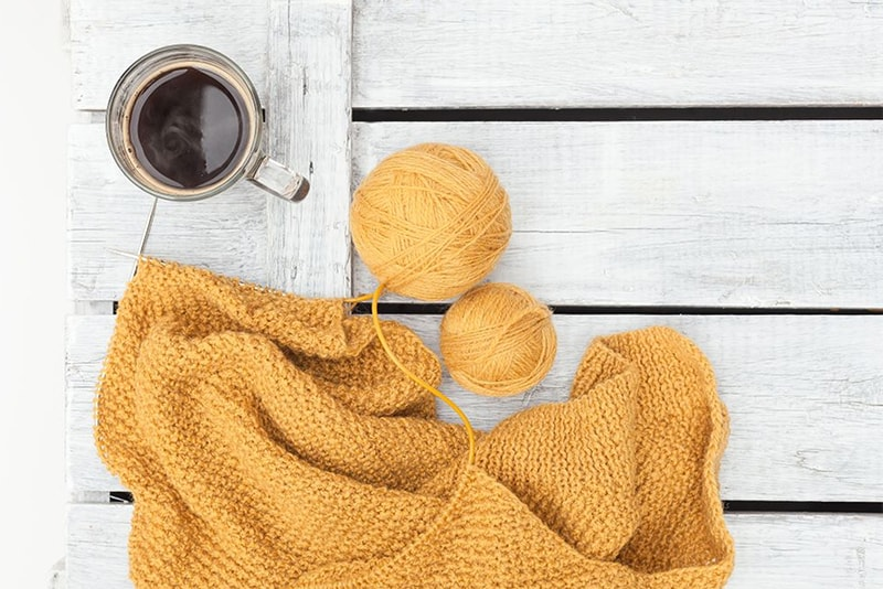 mustard sweater being knit on circular knitting needles