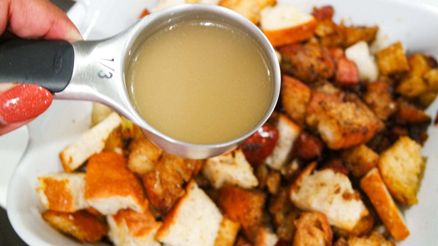 Pouring chicken broth into sausage stuffing.