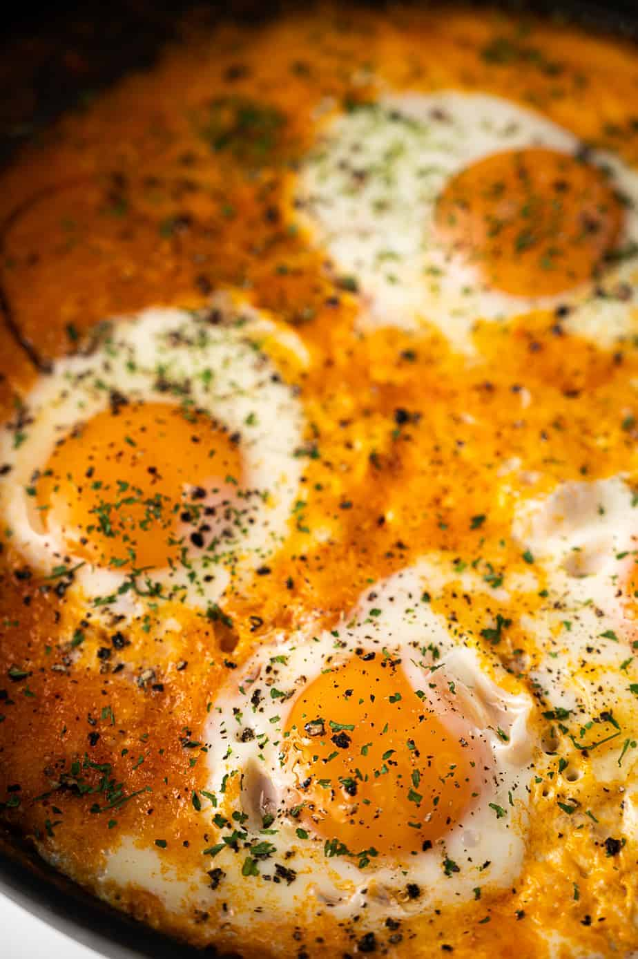 Eggs with parsley in a shakshuka