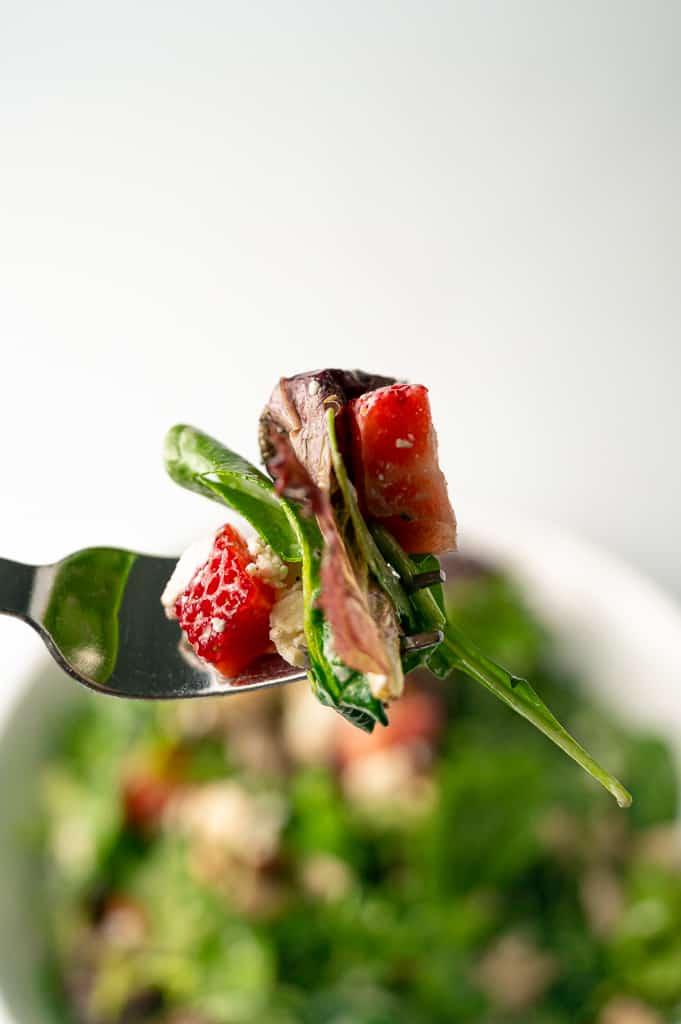 Strawberry pecan chicken salad on a fork.
