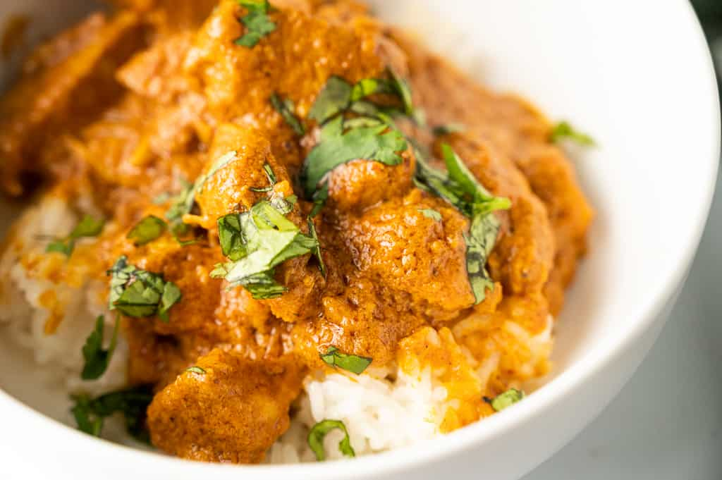 indian butter chicken in a bowl topped with cilantro
