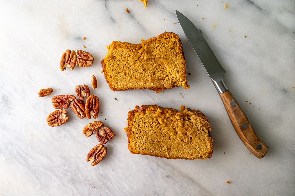 Flat lay of pecans, pumpkin bread and knife on marble board.