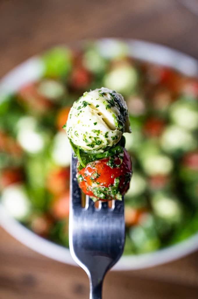 Mozzarella basil and tomato covered in chimichurri on a fork above kale caprese salad