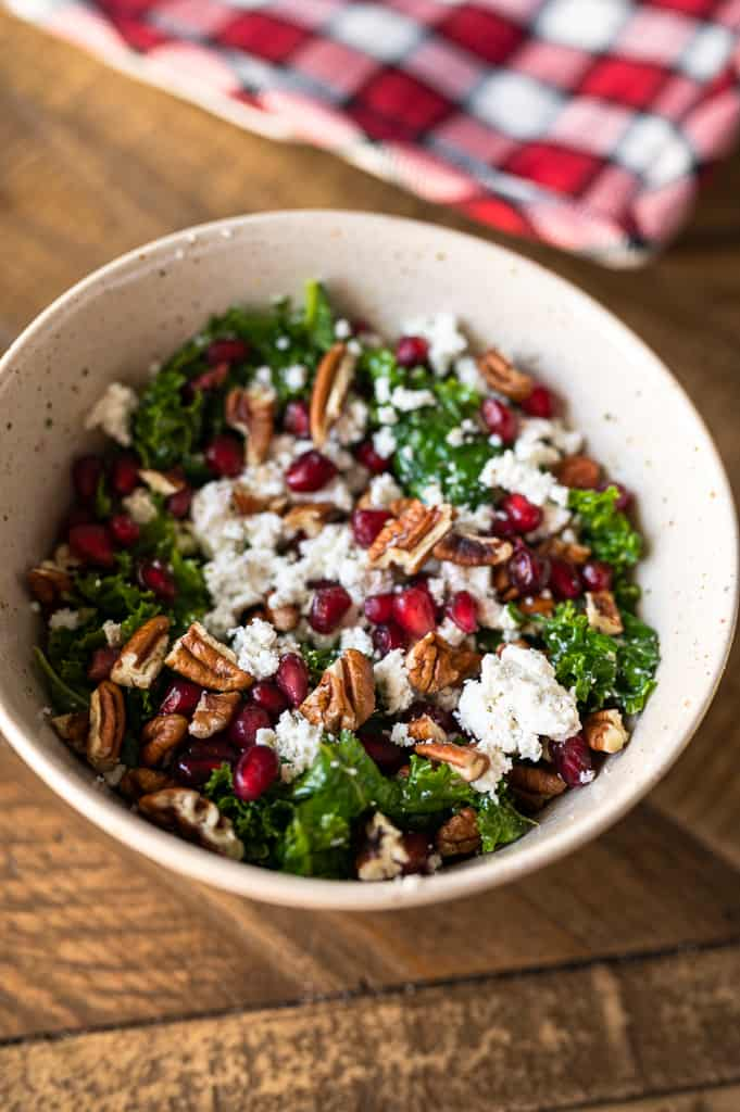massaged kale salad in a bowl with goat cheese and pecans
