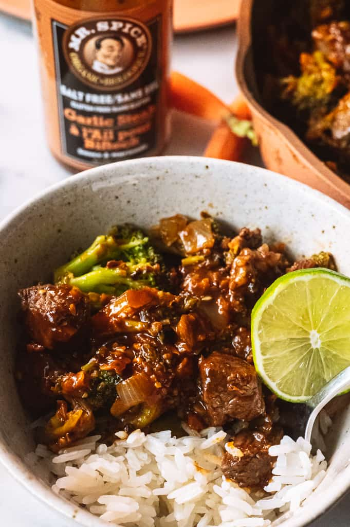 Beef and Broccoli in a bowl with a lime wedge and rice surrounded by Mr. spice bottle and pink pan