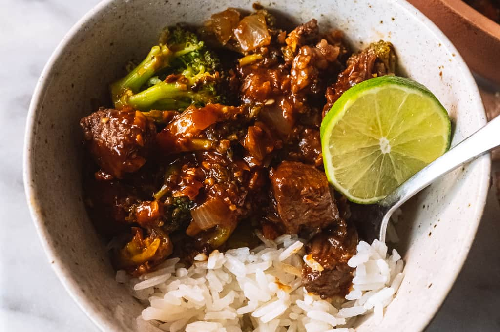 Beef and broccoli in a bowl with a lime and rice