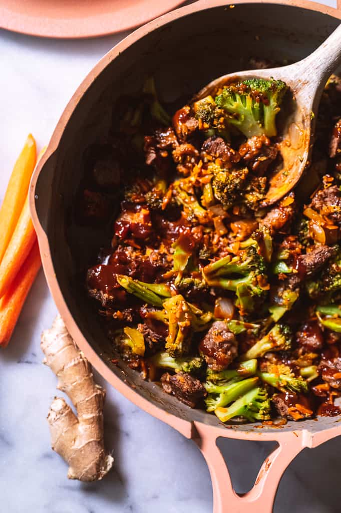 Beef and Broccoli in pan with wooden spoon.