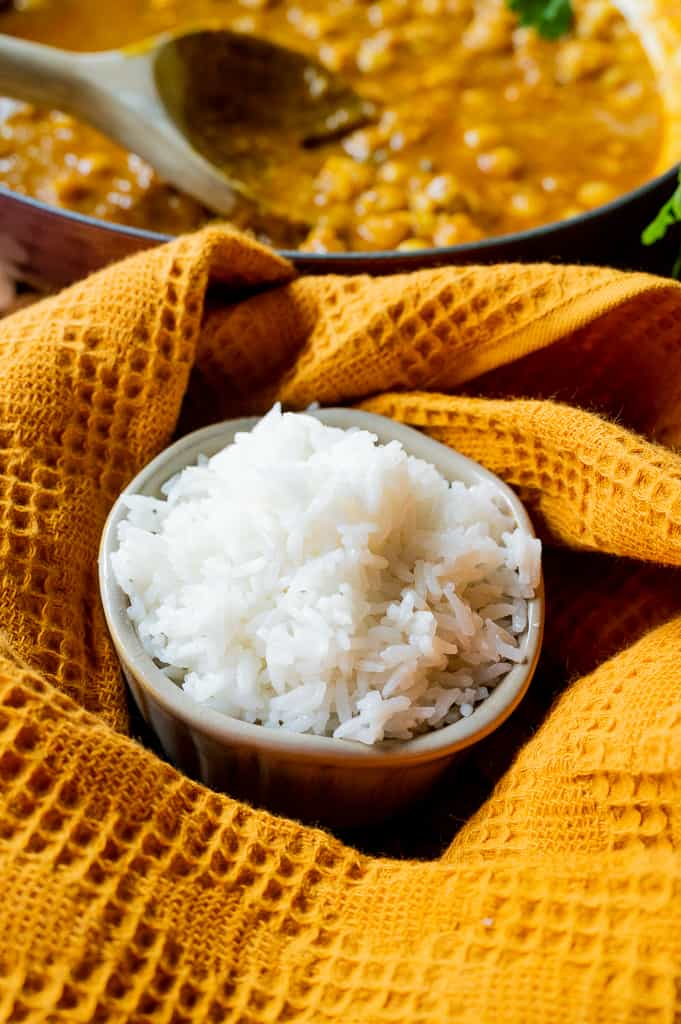 White jasmine rice in a bowl with curry behind