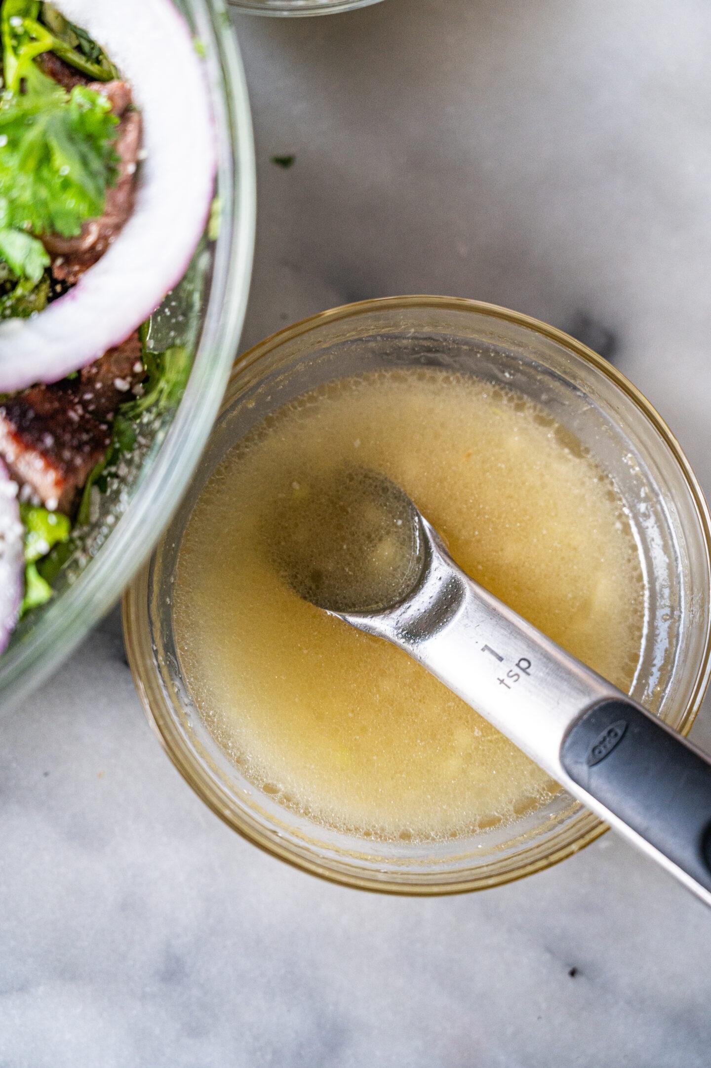 apple cider vinaigrette in a bowl next to a salad