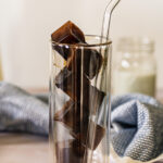 Frozen coffee ice cubes in tall double walled glass with a straw.