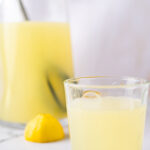 Glass of lemonade in front of a pitcher and slice of lemon