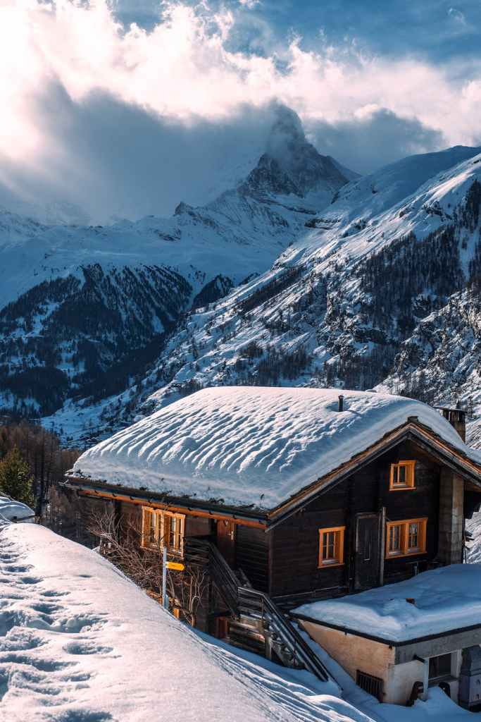 wooden house with snow on roof in winter mountainous terrain