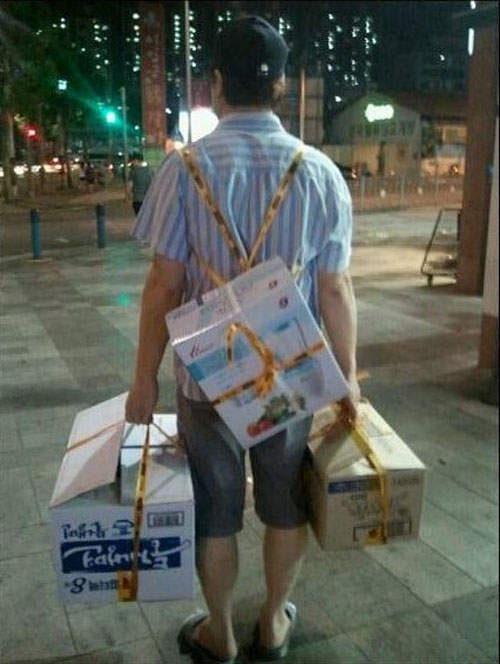 man carrying three boxes