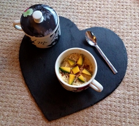 Porridge in pot on a black heart shaped slate