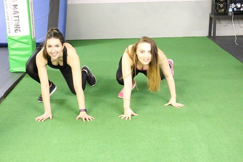 two girls on green floor background in gym
