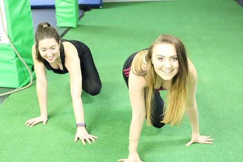 two girls on green floor backgroudn in gym