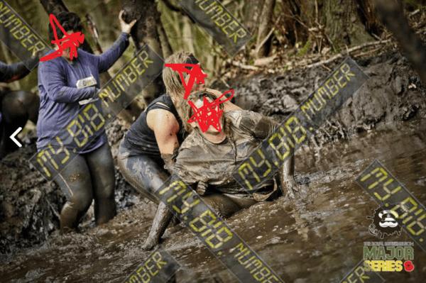 Women diving through mud in woods
