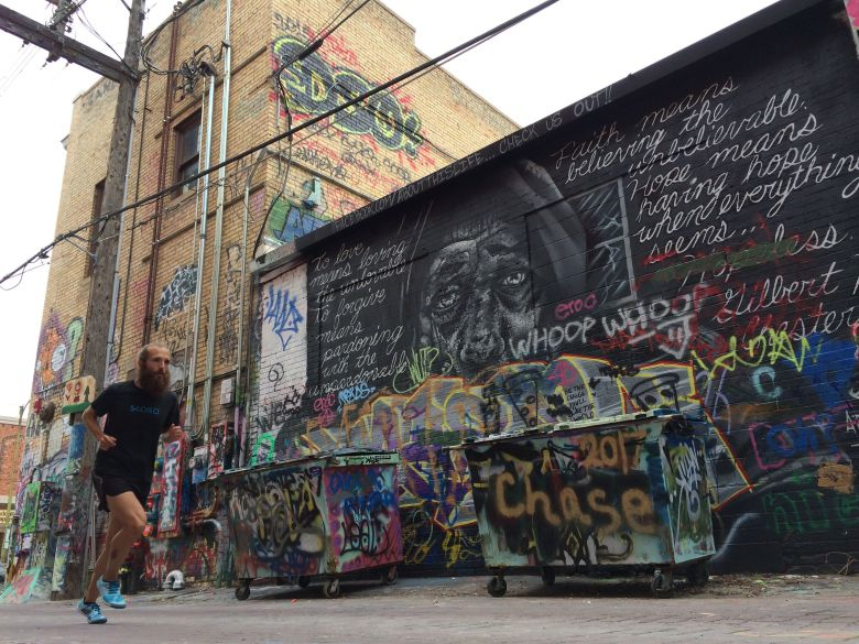 men running down graffiti alley