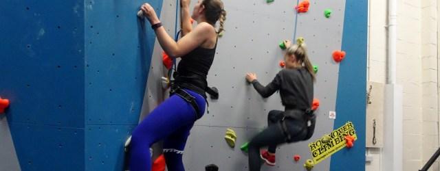 Girl climbing up rock climbing wall