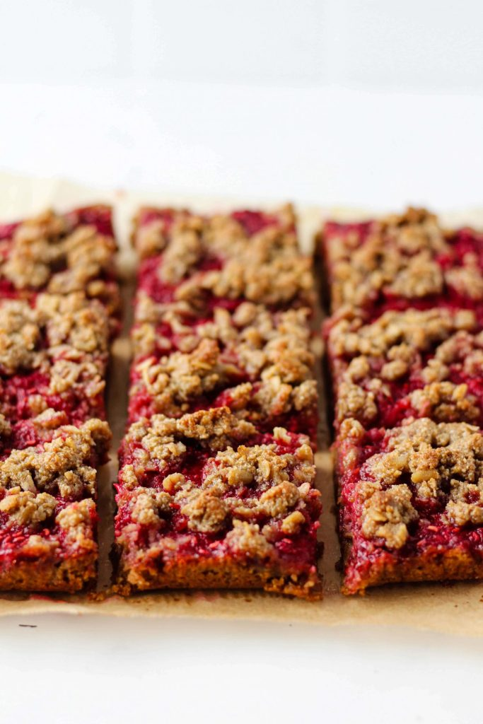 These Oat Raspberry Bars are like a berry crumble in bar form. They're simple to make and contain nourishing ingredients like oats, fresh raspberries, and almond butter. The recipe is gluten-free and can easily be made vegan. They're delicious on their own or served with a scoop of yogurt or vanilla ice cream!