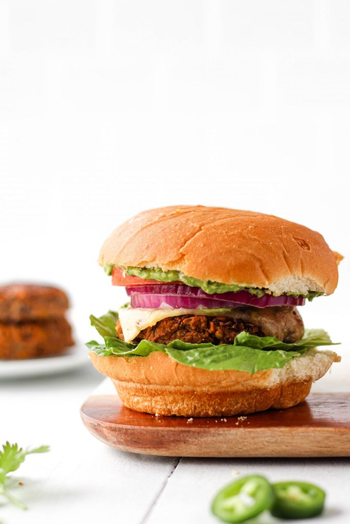 This spicy bean burger recipe is nutritious, delicious, and easy to make. Paired with homemade cilantro avocado sauce, this might just be the most flavourful vegetarian burger you'll ever try!