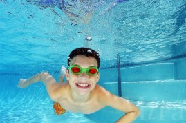 Boy swimming underwater in pool.