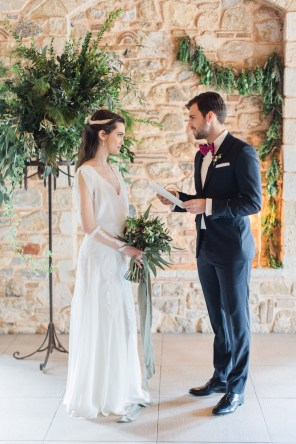 Bride and groom during their wedding ceremony reading their wedding vows surrounded by the decorations of Pyrgos Petreza in Athens.