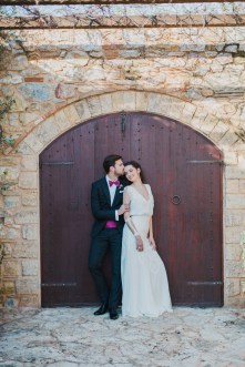 Bride and groom posing for elegant wedding day portraits with the backround of Pyrgos Petreza estate in Athens.