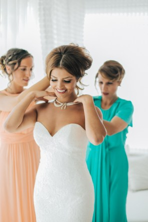 Professional wedding day portrait, beautiful smiling bride being dressed up by her mother and one of the bridesmaids.
