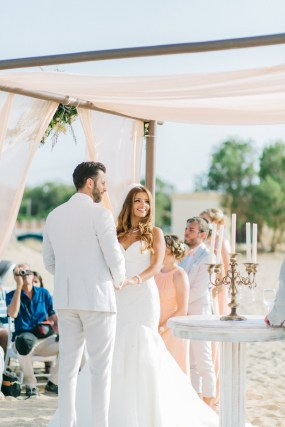 Professional wedding day photoshoot on a beach wedding ceremony, bride and groom getting married under the decorated canopy on one of the beaches in the area of Chania Crete.