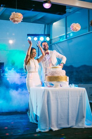 Wedding day reception portrait of bride and groom having fun when cutting the wedding cake at the start of their wedding reception in Crete.