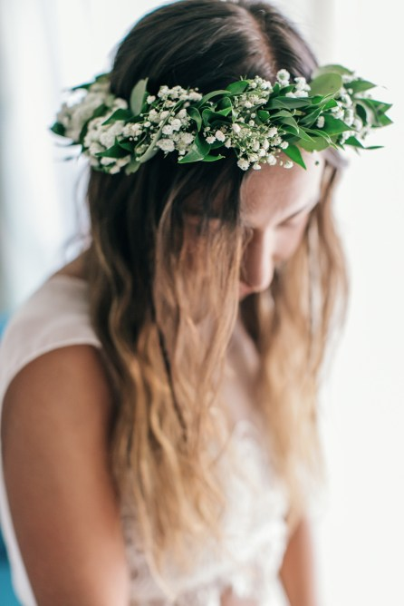 Beautiful boho bride wearing a handmade green flower wreath during bridal preparations for a beach ceremony.