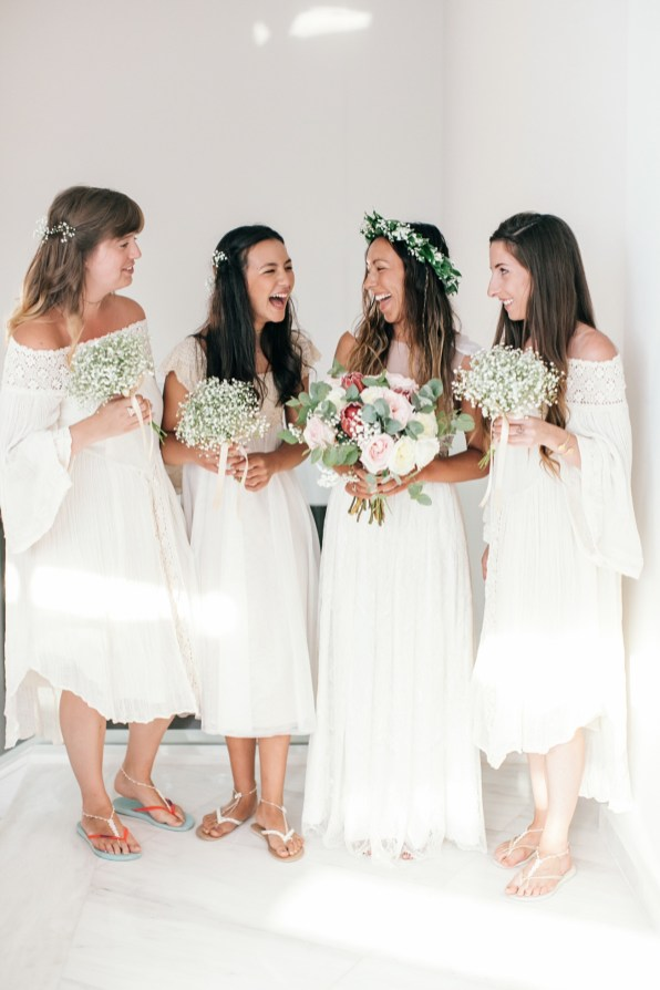 Portrait of a bride and bridesmaids laughing and posing for professional wedding dayportraits before they join the ceremony set up on the nearby beach.
