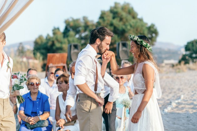 Portrait of the groom and bride before their symbolic beach wedding ceremony in Crete.