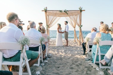 Bride and groom standing under the wedding canopy set up and decorated on the beach for a symbolic wedding ceremony.