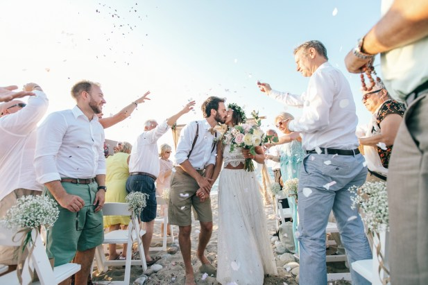 Bride and groom kissing while walking between their guests who are throwing petals and laughing.